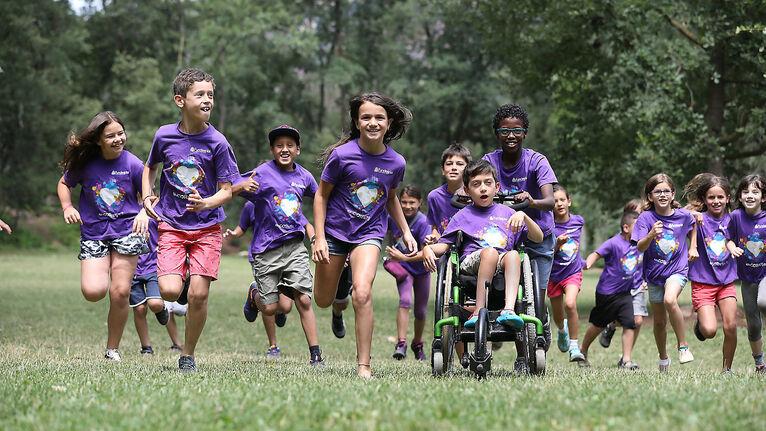Nen amb cadira de rodes, acompanyat d'altres nens i nenes de colònies, corrent pel bosc