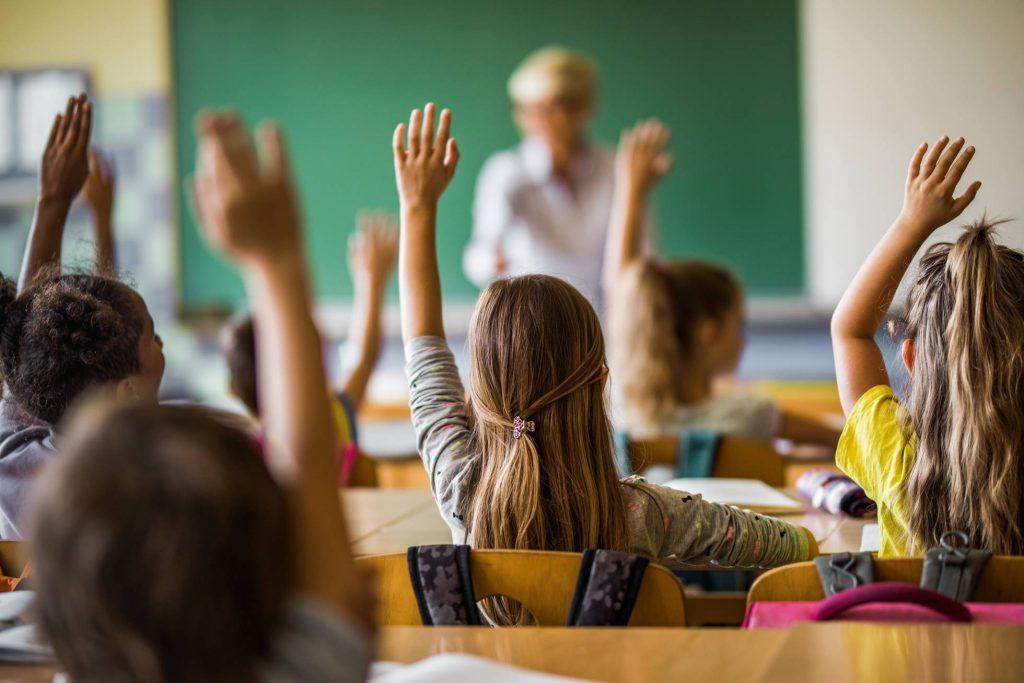 Alumnes de Primària a l'aula, amb les mans aixecades