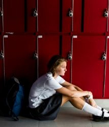 Noia asseguda davant de les guixetes d'una escola