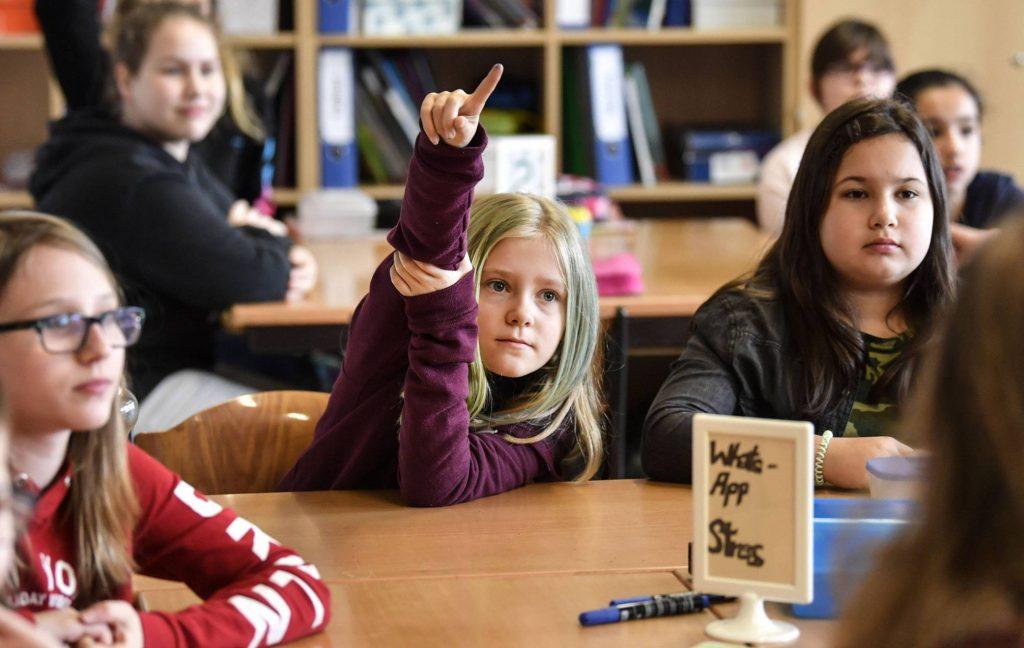 Nena aixecant el dit a l'escola