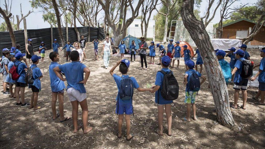 Grup de nens i nenes en cercle amb monitors en campament d'estiu