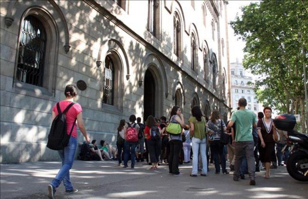 Universitat de Barcelona. Vista des del carrer, aglomeració d'estudiants davant de la porta